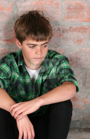 Serious Teen stock photo, Serious teenager sitting alone against a brick wall by Vanessa Van Rensburg