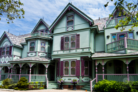 Old Victorian house stock photo, Beautiful big old nostalgic historic wooden green with purple Victorian house building with porch. by Paul Hakimata
