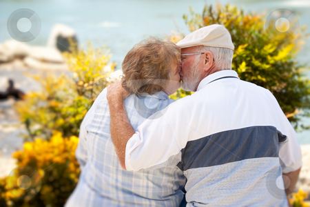 Happy Senior Couple in The Park stock photo, Happy Senior Couple Kissing Each Other in The Park. by Andy Dean