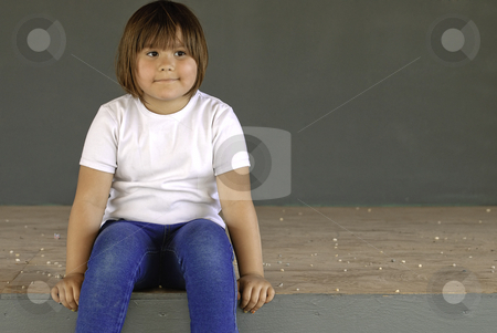 Waiting stock photo, A young five year old girl is sitting on a stage waiting for something. by Richard Nelson