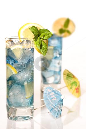 Parasol cocktail stock photo, Blue long drink cocktails decorated with mint, lemon, parasols by Anneke