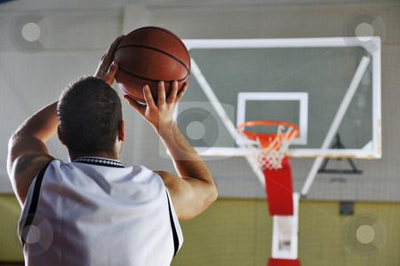 Basketball player shooting stock photo, Basketball game playeer shooting on basket indoor in gym by Benis Arapovic