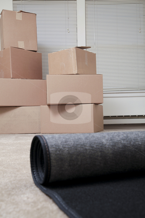 Just moved in stock photo, A rug being unrolled in an empty house with boxes in the background by Christy Thompson