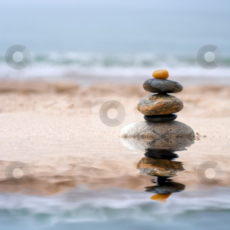 Smooth Stacked Stones stock photo, A pile of round smooth zen like stones stacked in the sand at the beach. by Todd Arena