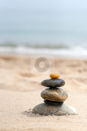 Smooth Stacked Rocks stock photo, A pile of round smooth zen rocks stacked in the sand at the beach. by Todd Arena