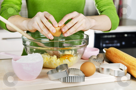 Baking cookies stock photo, Cracking egg into mixing bowl making cookies by Elena Elisseeva