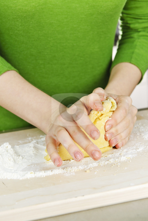 Hands kneading dough stock photo, Hands kneading ball of dough with flour on cutting board by Elena Elisseeva