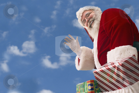 Santa Claus against a baby blue sky stock photo, Santa Claus with bag of presents waves against a background of Cumulus clouds in an azure blue sky by Gabe Palmer