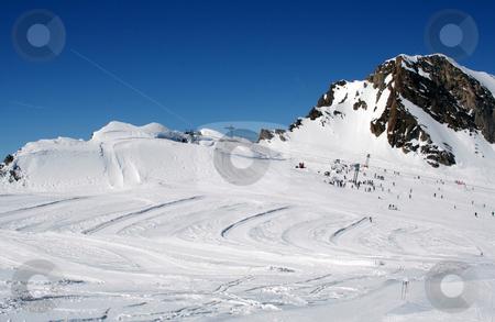 Alpine ski slope and skiers stock photo, Scenic view of Alpine ski ski with skiers and mountain in background, Switzerland. by Martin Crowdy