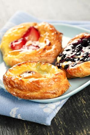 Three fruit danishes stock photo, Closeup of three fruit danish desserts on a plate by Elena Elisseeva
