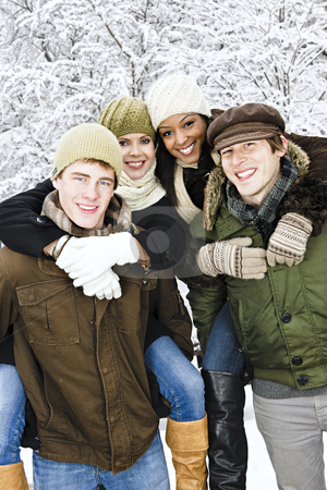 Group of friends outside in winter stock photo, Group of young friends giving piggy back rides outdoors in winter by Elena Elisseeva