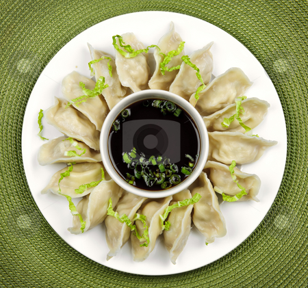Steamed dumplings and soy sauce stock photo, Plate of steamed dumplings with soy sauce from above by Elena Elisseeva