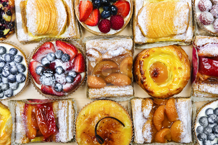 Assorted tarts and pastries stock photo, Background of assorted fresh sweet tarts and pastries from above by Elena Elisseeva