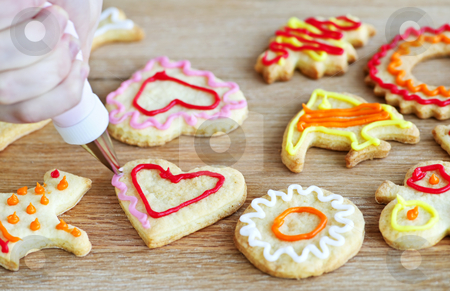 Decorating cookies stock photo, Decorating homemade shortbread cookies with icing from piping bag by Elena Elisseeva
