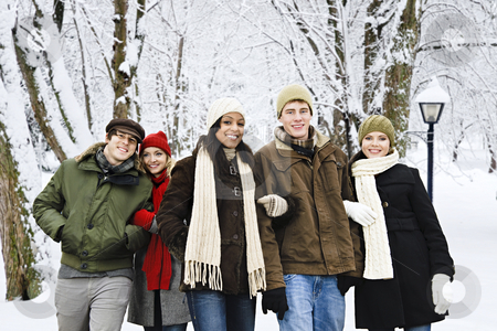Group of friends outside in winter stock photo, Group of diverse young friends walking outdoors in winter park by Elena Elisseeva