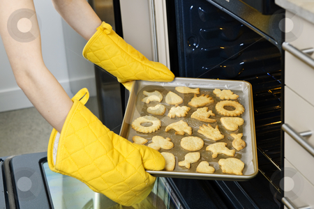 Taking cookies from oven stock photo, Taking fresh baked shortbread cookies from oven in kitchen by Elena Elisseeva