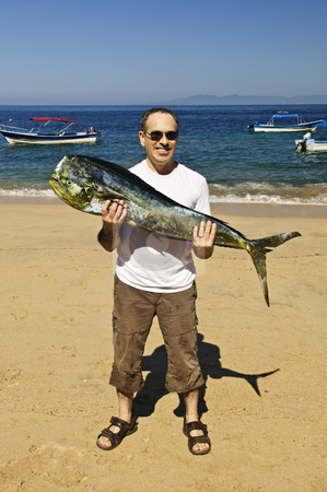 Tourist holding big fish on beach stock photo, Happy tourist holding his big fish catch after fishing trip in Mexico by Elena Elisseeva