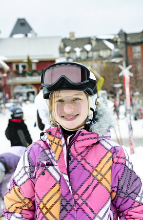 Happy girl in ski helmet at winter resort stock photo, Portrait of happy teenage girl in ski helmet and goggles at winter resort by Elena Elisseeva
