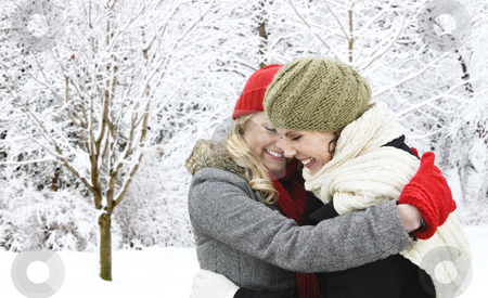 Two girl friends hugging outside in winter stock photo, Portrait of two young girl friends hugging outdoors in winter by Elena Elisseeva