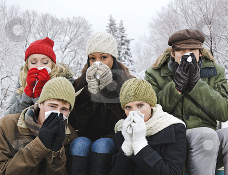 Group of friends with colds outside in winter stock photo, Group of diverse young friends blowing noses outdoors in winter by Elena Elisseeva