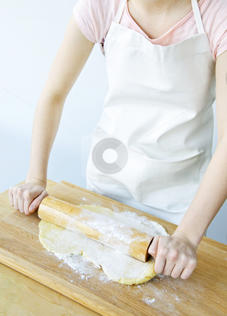 Rolling out cookie dough stock photo, Spreading out cookie dough with wooden rolling pin by Elena Elisseeva