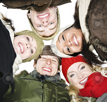 Group of friends outside in winter stock photo, Faces of happy diverse young friends from below by Elena Elisseeva