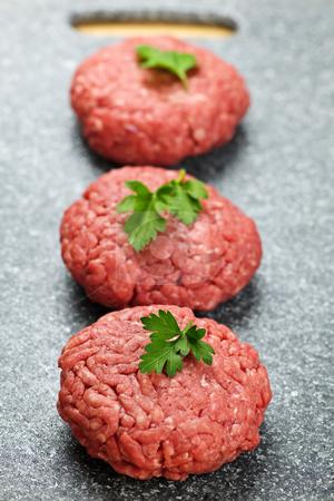 Hamburger patties stock photo, Three ground beef hamburger patties on cutting board by Elena Elisseeva