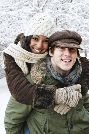 Couple having fun outside in winter stock photo, Portrait of couple having piggyback ride outdoors in winter by Elena Elisseeva