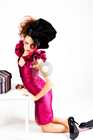 Young Woman in Avant Garde Attire stock photo, A young woman dressed in avant garde attire and kneeling near a hat box. She is wearing a hat and has cosmetic artwork on her right temple. Horizontal shot. by Angela Hawkey