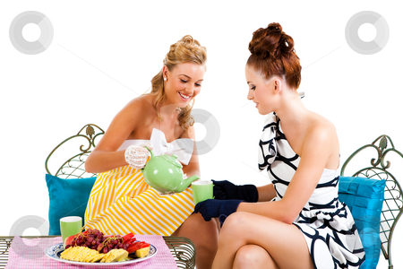Two Young Women Having Tea - Isolated stock photo, Portrait of two young women sitting at a table having tea. They are formally dressed and wearing gloves. Horizontal shot. Isolated on white. by Angela Hawkey