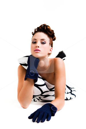 Young Woman in Haute Couture Attire - Isolated stock photo, Young woman with an elaborate hairstyle and wearing a black and white dress with a large bow. She is lying down and only viewable from the waist up. Vertical shot. Isolated on white. by Angela Hawkey