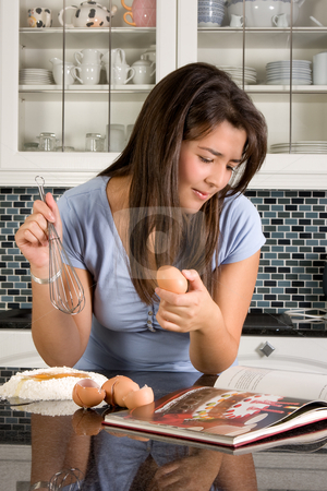 New recipe stock photo, Young woman reading a recipe in a cookbook by Anneke