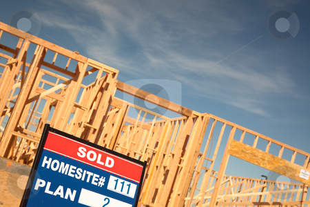 Sold Lot Sign at New Home Construction Site stock photo, Sold Lot Real Estate Sign at New Home Framing Construction Site Against Deep Blue Sky. by Andy Dean
