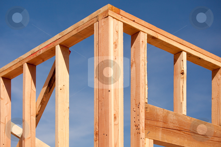 New Home Construction Framing stock photo, New Residential Home Construction Framing Site Against Blue Sky. by Andy Dean