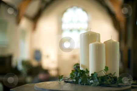 Church candles stock photo, A narrow depth of field image of the interior of a church focusing only on three white candles by Stephen Gibson