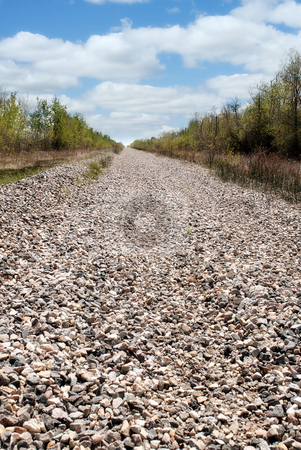Long Rocky Path stock photo, A long rocky path situated where railroad tracks used to be, shot on a partly cloudy day. by Richard Nelson