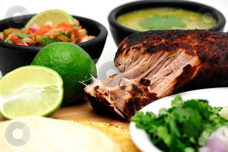 Carnitas stock photo, Pork roast cooked to make Mexican carnitas with fresh tortilla's' chunky tomato salsa and salsa verde and sliced limes by Lynn Bendickson