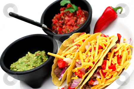 Hard Shell Taco's stock photo, Three hard shell taco's with sides of fresh salsa and guacamole served on a white plate and a single red chili pepper on the side. by Lynn Bendickson