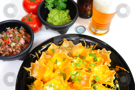 Beer And Nacho's stock photo, A plate of hot nacho's and a glass of cold beer on the side with bowls of fresh spicy salsa and guacamole and the cap from the beer bottle by Lynn Bendickson