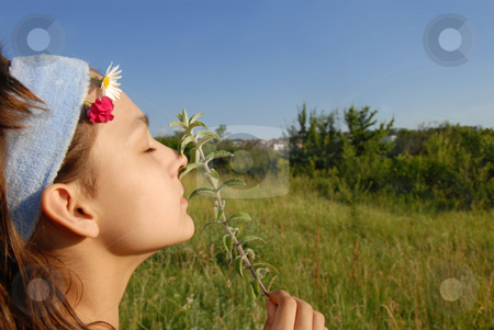 Young girl portrait outdoor stock photo, Young girl portrait side view smelling a plant on green meadow at summer by Julija Sapic