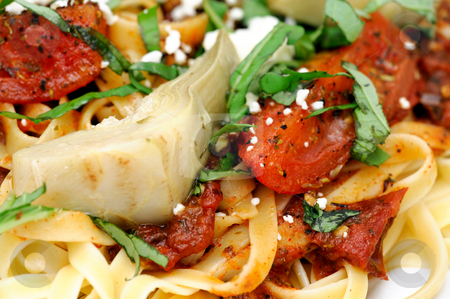 Close-up Fettuccini With Roasted Tomato And Basil stock photo, Fettuccini topped with tomatoes roasted in olive oil and italian herbs and spices with marinated artichoke hearts sliced fresh basil and feta cheese by Lynn Bendickson