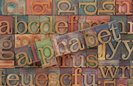 Alphabet in vintage wood type stock photo, The word of alphabet across a background of vintage wooden letterpress type blocks, stained by color inks by Marek Uliasz
