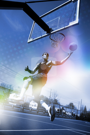Basketball Slam Dunk stock photo, A basketball player drives to the hoop for a slam dunk with abstract rainbow lens flare and halftone effects. by Todd Arena