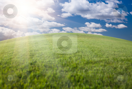 Green Grass Field, Blue Sky and Sun stock photo, Lush Green Grass Field, Blue Sky with Clouds and Sun by Andy Dean