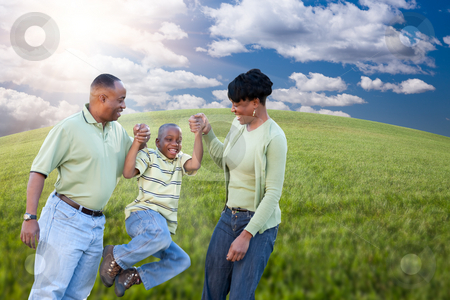 Family Over Clouds, Sky and Grass Field stock photo, Happy African American Family Playing Over Clouds, Sky and Arched Horizon of Grass Field. by Andy Dean