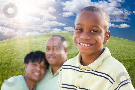 Handsome African American Boy with Parents stock photo, Handsome African American Boy with Proud Parents Standing Over Clouds, Sky and Arched Horizon of Grass Field. by Andy Dean