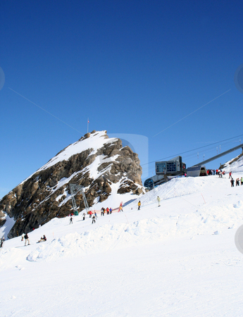 Alpine ski lift and slope stock photo, Scenic view of Alpine ski lift and slope with rocky mountain peak, Switzerland. by Martin Crowdy
