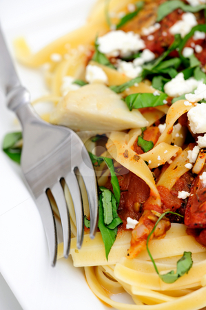 Fettuccini With Roasted Tomato And Basil stock photo, Fettuccini topped with tomatoes roasted in olive oil and italian herbs and spices with marinated artichoke hearts sliced fresh basil and feta cheese by Lynn Bendickson