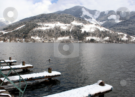 Alpine lake and mountains stock photo, Scenic view of Alpine lake and mountains under cloudscape with snow covered jetty in foreground. by Martin Crowdy