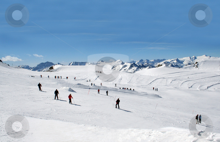 Skiers on Alpine ski slope stock photo, Scenic view of group of skiers on Alpine ski slope with blue sky background. by Martin Crowdy